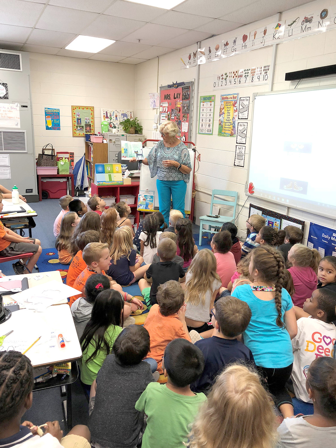 Carolyn Ingram, CCS board member and Rotarian, reads to first-grade classes of Mrs. Shaver, Mrs. Lay, and Mrs. Robbins at Yates Primary.