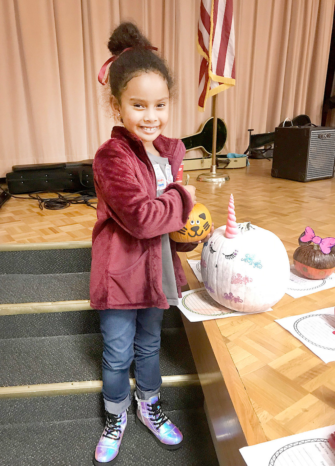 Kate Guevara shows off her storybook pumpkins and her shiny shoes during the 2018 Fall Harvest Hoedown, at Blythe-Bower Elementary.