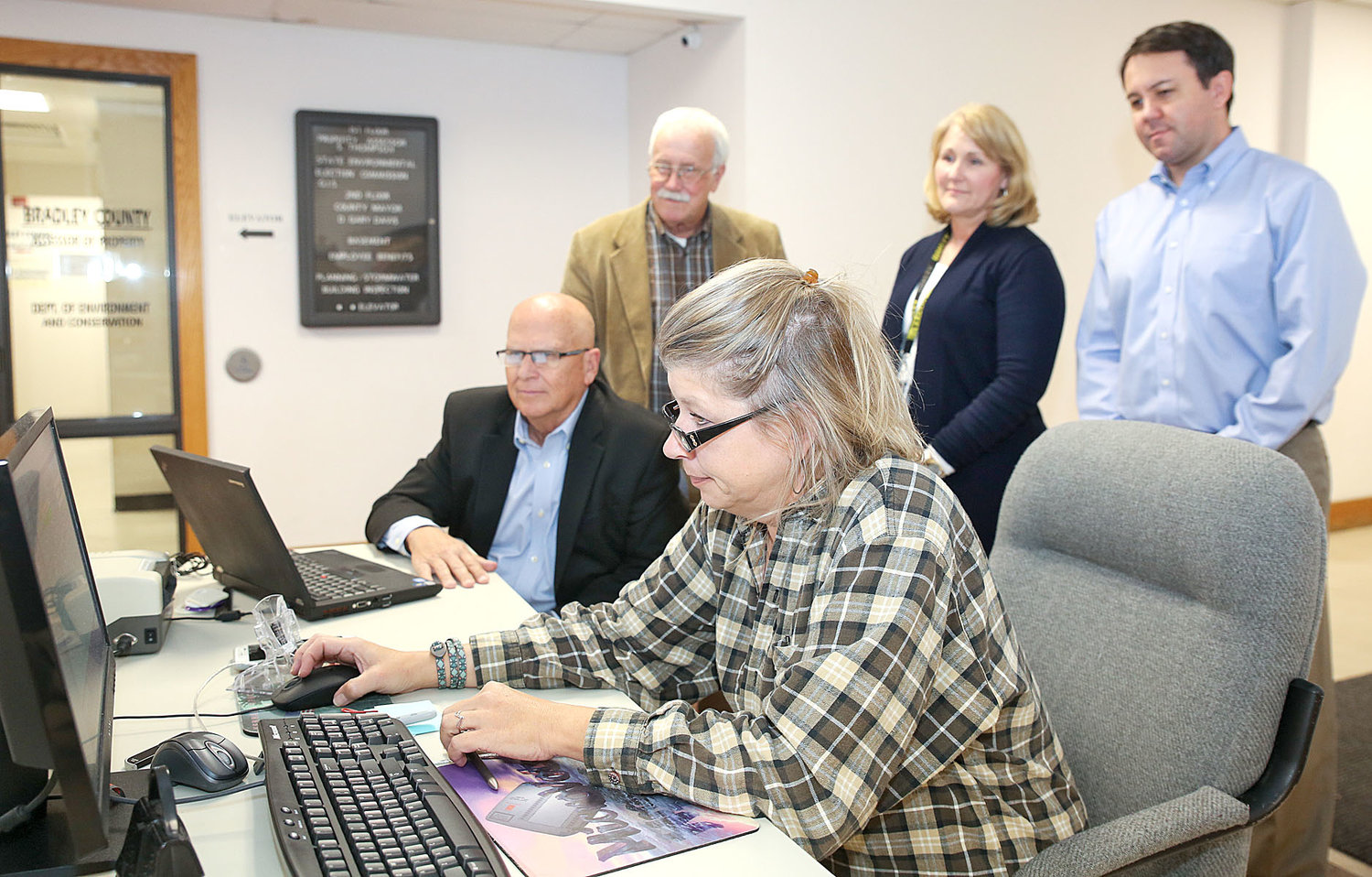 BRADLEY COUNTY ADMINISTRATOR of Elections Fran Green, center, watches her computer closely as the voting precincts close and tabulation results begin to roll in on election night at the Bradley County Election Commission. Seated from left are Joe Reed, CPA and consultant to the Bradley County Election Commission and Green. Standing, from left, are Commissioners Dana Burgner, Cristy Schuch and Travis Henry.