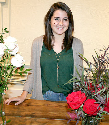 CHEYENNE HAMILTON, owner of Stems at Five Points, stands amid some of her floral designs on her third day of business. Having a master's degree in accounting allows Hamilton to crunch the numbers of her business while also running it and aiding customers. At just 24, Hamilton has already grown her business' social media presence and continues to receive orders for upcoming events in 2019.