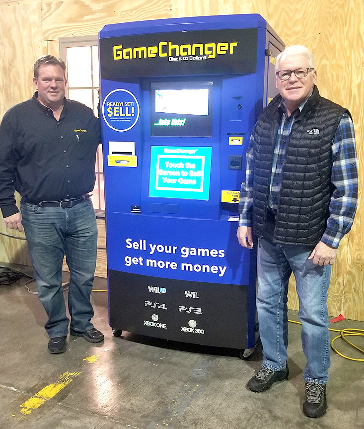 BRENT HALL, left, and Jerry Stout, right, two local entrepreneurs, stand next to their collaborative creation, GameChanger, a kiosk that scans used games, determines their buyback value and presents it to users within 15-20 seconds.