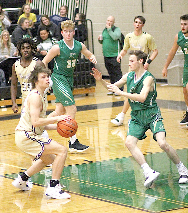 BRADLEY CENTRAL sophomore Tucker Greene (with ball) looks to dish to a teammate during Friday evening's 63-37 victory over Rhea County in the East-West Classic at East Hamilton High School. Bears Ricky McCleary (33) and Mason Rothwell (back) look on at the action.