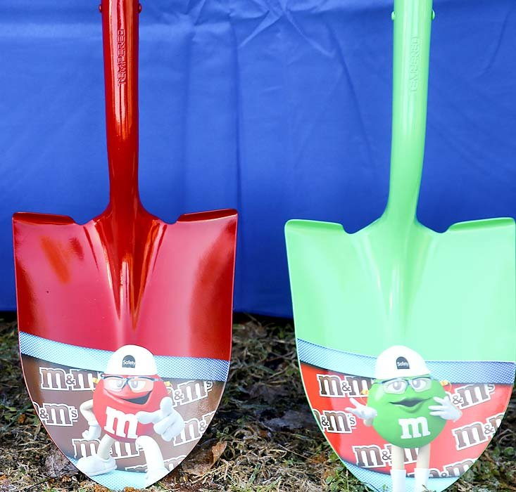 THE RED AND GREEN M&M shovels sit propped against a table before Tuesday's groundbreaking ceremony.