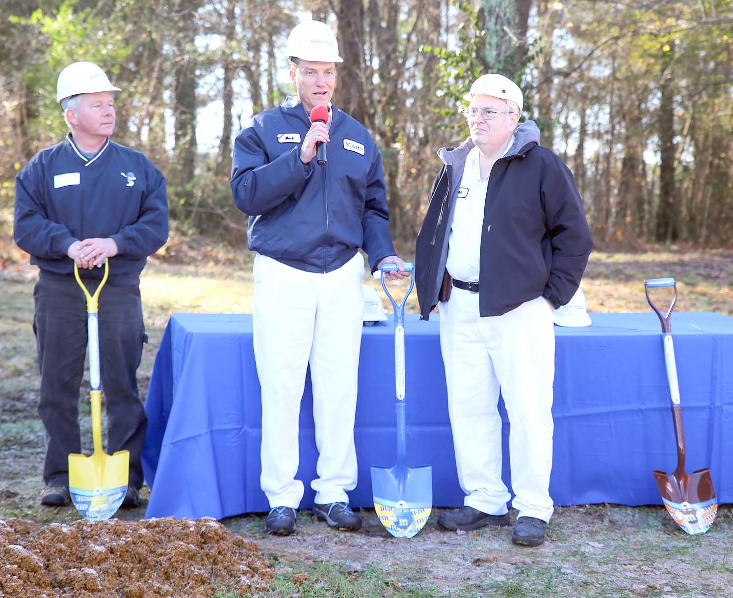 SITE DIRECTOR MACK PHILLIPS, center, asks 40-year Mars employee Rick Joines, right, to fill in for one of the dignitaries not in attendance, and take part in the official groundbreaking ceremony. Also pictured is former site director Todd Farell, left.