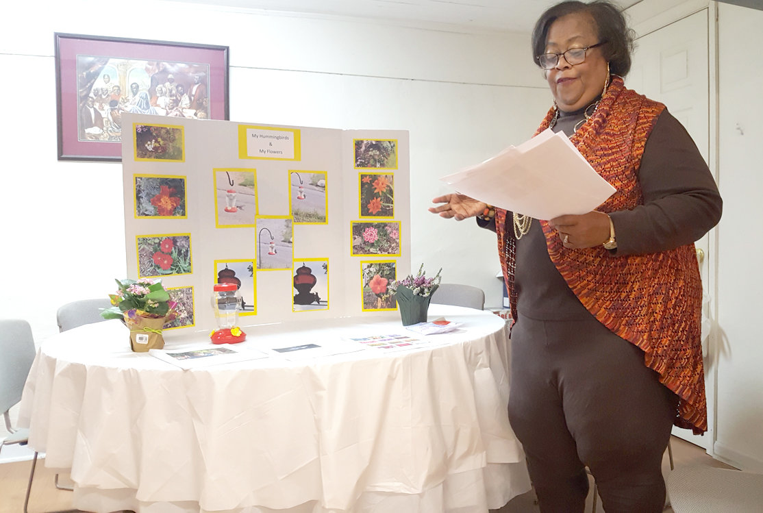 "Jackie Westfield, hostess, presented a program on ""Attracting Hummingbirds to Your Yard.""  She is standing in front of her educational display board with handouts provided to the members.  Kalanchoe and heather plants are some flowers that attract hummingbirds."