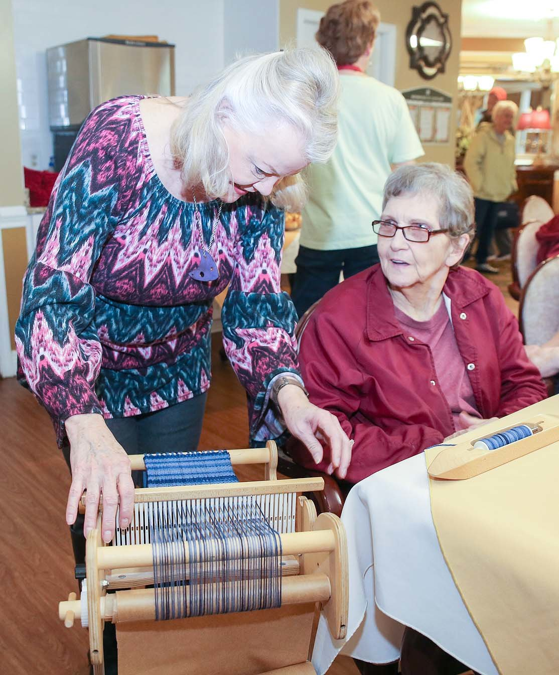 "PHYLLIS NARUS, owner of R&M Yarns in Georgetown and member of the Scenic Valley Handweavers Guild, left, shows Morningside of Cleveland resident Delores Miller some weaving on a loom at the ""Art For Your Heart"" event on Wednesday."