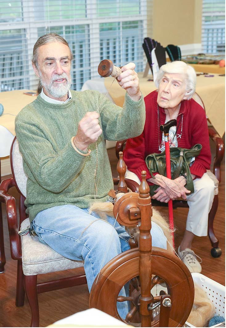 STEVE PRENTICE, a member of the Scenic Valley Handweavers Guild, left, demonstrates spinning yarn on an 80-year-old spinning wheel to Morningside of Cleveland resident Blanche Vaden.