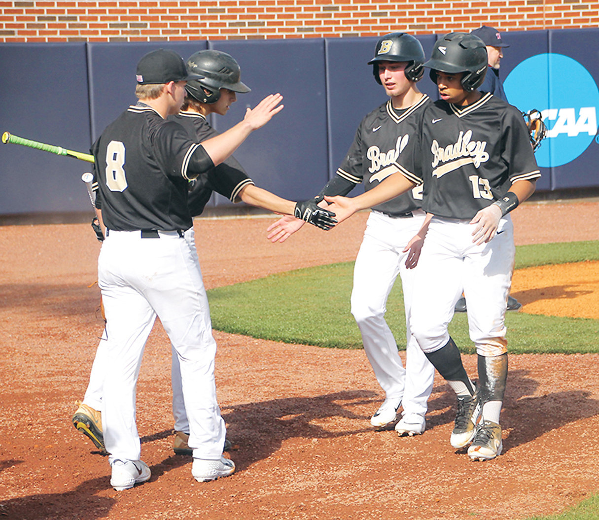 BRADLEY CENTRAL baserunners Iverson Vasquez (13) and Caden Sherlin (2) are greeted by teammates Dylan Standifer (8) and Ryan Giovengo after scoring runs in the opening game Tuesday at Olympic Field, on the Lee University campus.