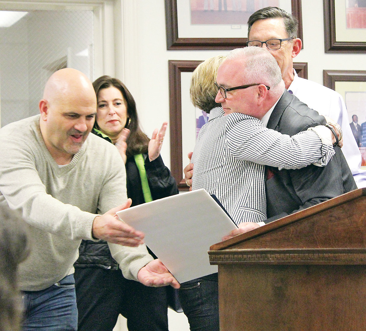 MAYOR KEVIN BROOKS hugs Julianne Wolf after reading a proclamation declaring Thursday, March 14, 2019, as Carrie Wolf McConnell Day. McConnell, who died in 2016, received a heart transplant when she was 7 years old.