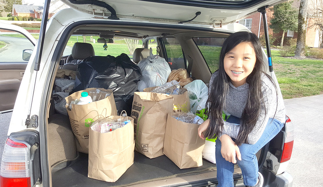 ELLIE LU FANNON poses alongside the  bags of recyclables she and her mom collected in their community. They hope to spread the word about recycling's benefits, and help introduce the service to their peers.