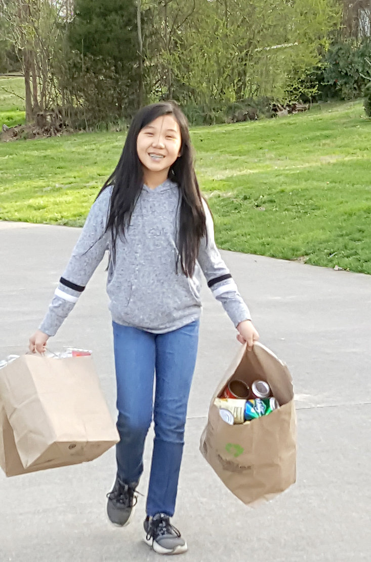 HOLDING BAGS of recyclables, Ellie Lu Fannon, a local sixth-grader, displays her dedication toward recycling and the healthy benefits it brings to the community.