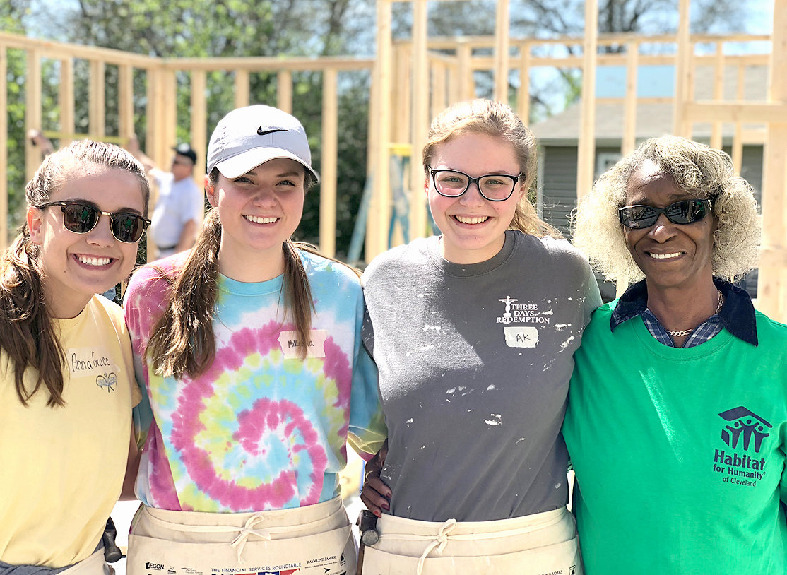 HABITAT FOR HUMANITY of Cleveland attracts a diverse crowd of volunteers, including students. From left are Anna Grace Jackson, Mikayla Beasley, Annie Kate Gibson and a Habitat homeowner, Eyvonne Vance.