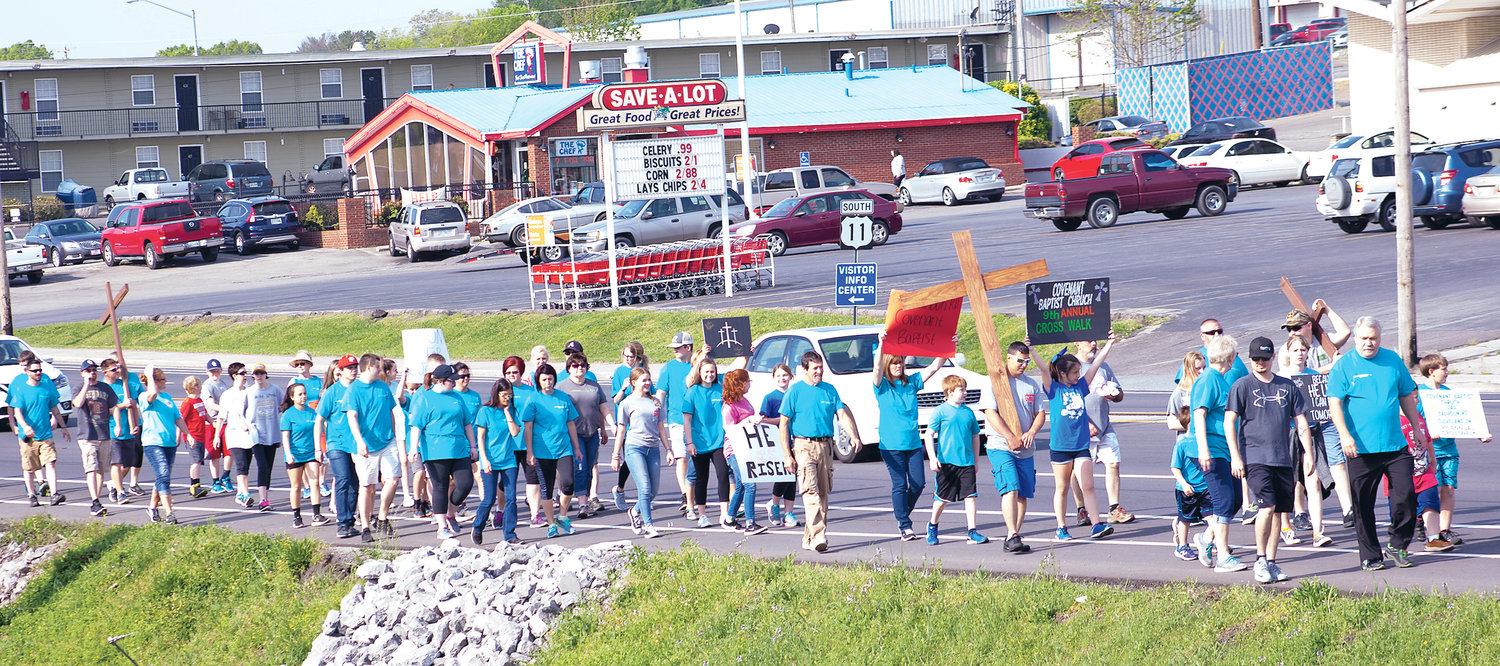 MEMBERS OF COVENANT Baptist Church stroll along Keith Street, during a previous Easter Cross Walk. This year's 12th annual walk will begin at 10:30 a.m. Saturday in the Village Green parking lot, and advance along Keith Street to Farmland Corner near Bradley Square Mall.