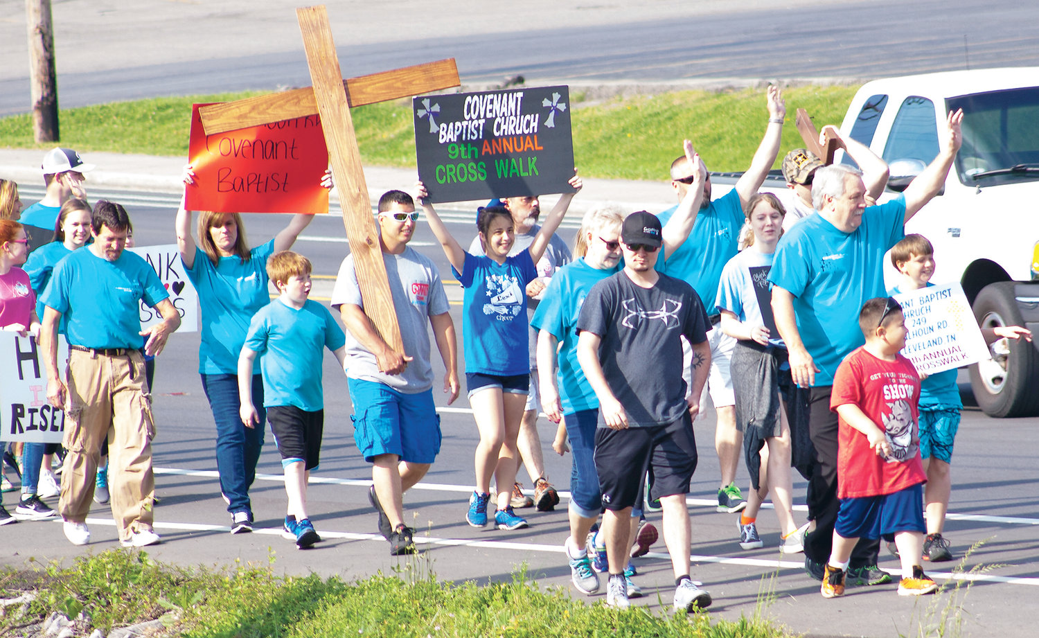 COVENANT BAPTIST'S Youth Ministry members are enthusiastic participants in the congregation's annual Easter Cross Walk each year. Here, participants in a previous walk advanced from The Village Green to Farmland Corner, carrying the wooden cross.