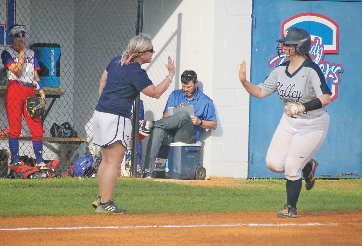 WALKER VALLEY head coach Lauren Limburg, left, high-fives Hannah Kate Singleton as she rounds the bases after blasting a two-run home run Wednesday, as the Feisty Fillies blanked Cleveland 5-0 at Brenda McKenzie Lawson Field.