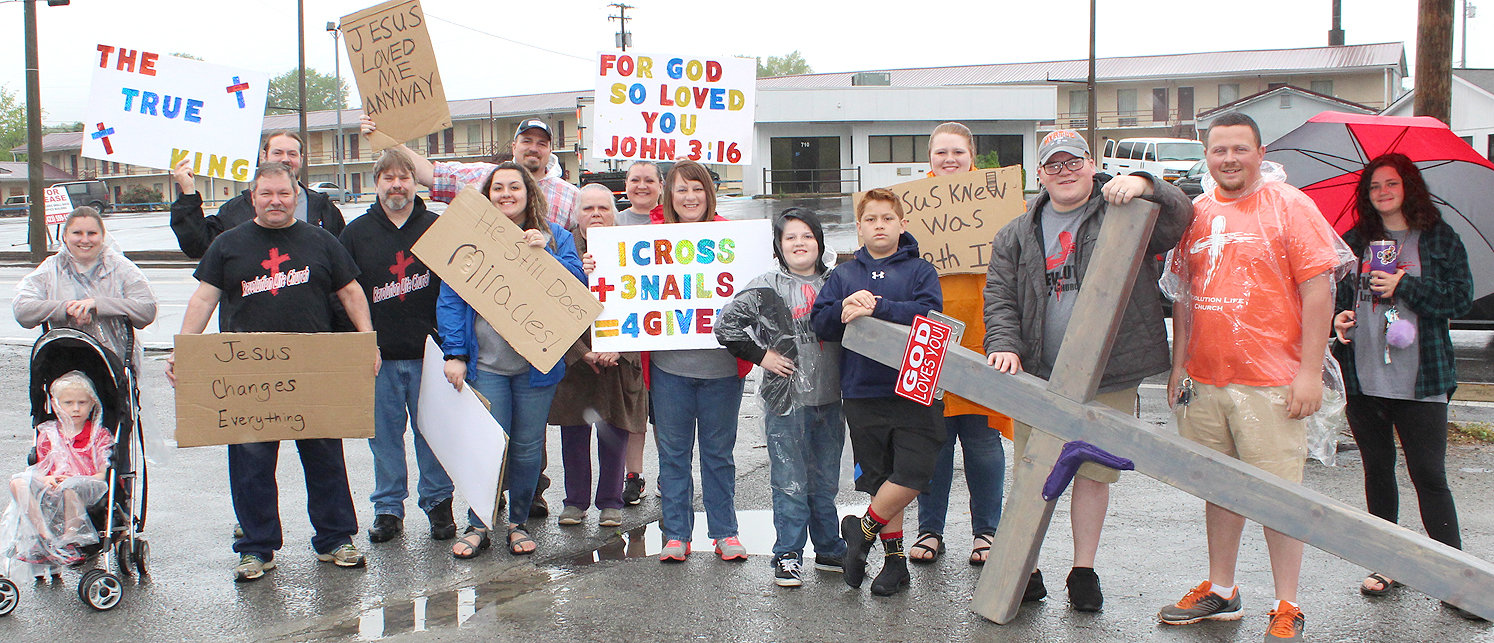 "MEMBERS OF REVOLUTION LIFE CHURCH prepare to begin their Cross Walk through Cleveland on Good Friday. Pastor Anthony Traylor is shown in the center, on the back row, holding the ""Jesus loved me anyway"" sign."
