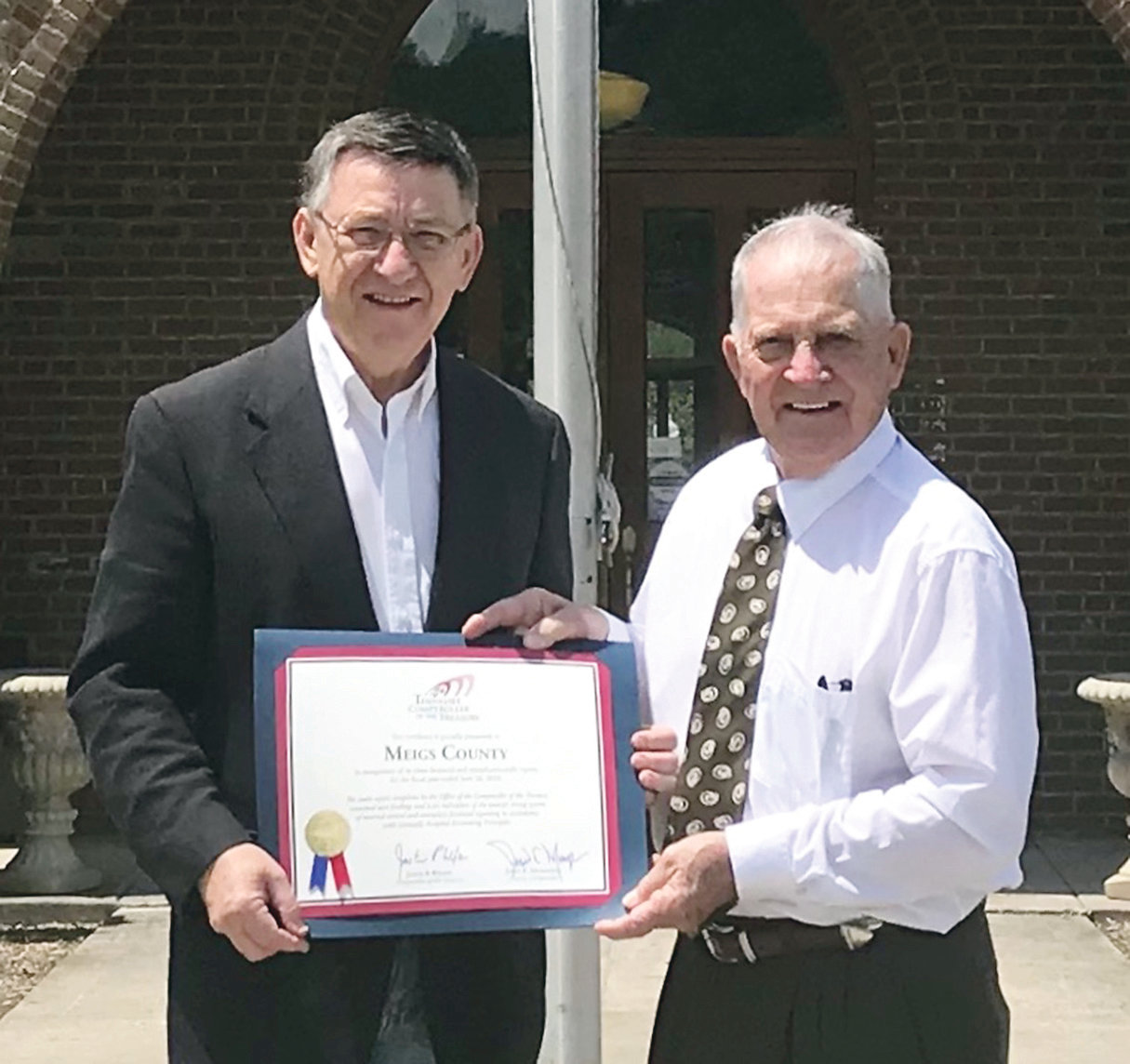 STATE REP. DAN HOWELL, left, presents a Certificate of Achievement to Meigs County Mayor Bill James on behalf of the Tennessee Comptroller's Office. The recognition honors the Meigs County mayor's office and finance department for a clean audit as conducted by the state office. Also honoring Meigs County government was state Sen. Mike Bell who could not attend the certificate presentation.