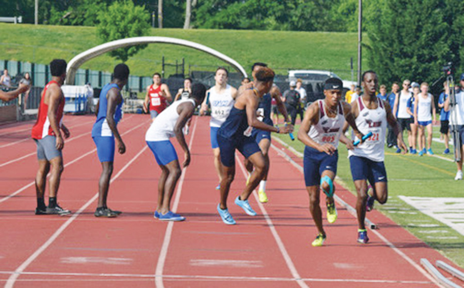 LEE UNIVERSITY'S Siphosethu Boya (left) receives the baton from Jeremiah McCain to begin the third leg of the 4x400-meter relay at the recent Gulf South Conference Championships.