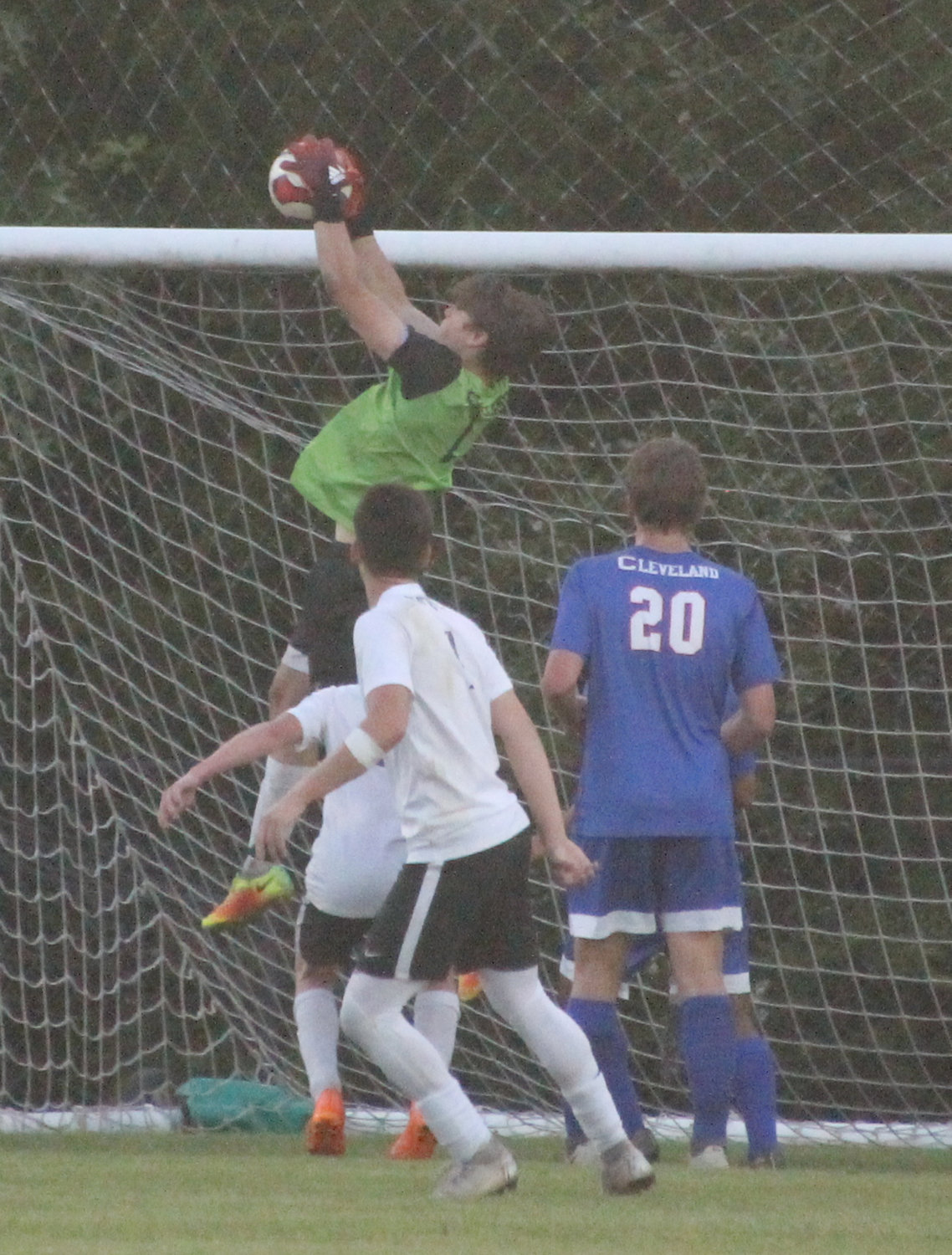 CLEVELAND HIGH junior goalkeeper Will Woodruff, center, makes one of his 12 saves in Tuesday evening's 2-0 shutout of Rhea County in the Region 3-AAA semifinal match at the Great Cleveland Soccer Complex.
