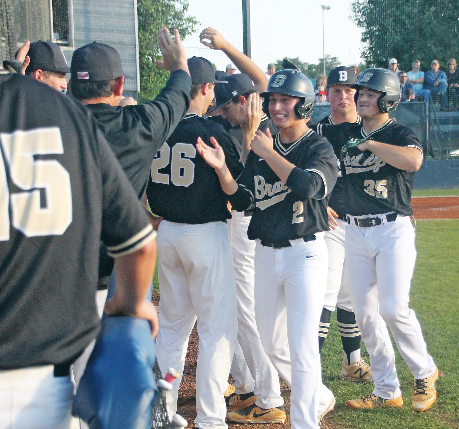 BRADLEY CENTRAL junior Riley Black (35) is greeted by teammates after blasting a two-run homer which also scored Caden Sherlin (2) in the second inning of Wednesday evening's 7-3 victory at Soddy-Daisy to claim the Region 3-AAA championship.