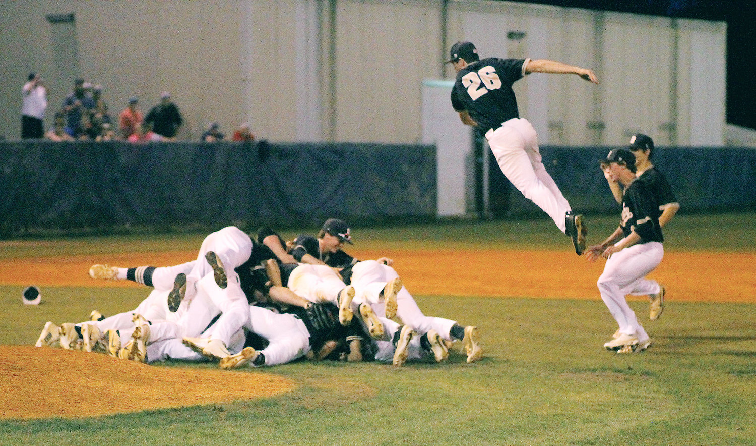BRADLEY CENTRAL junior Logan Weeks (26) gets some air as he dives into the celebration dogpile after the Bears claimed their third Region 3-AAA Championshp in the last four years Wednesday evening in Soddy-Daisy.