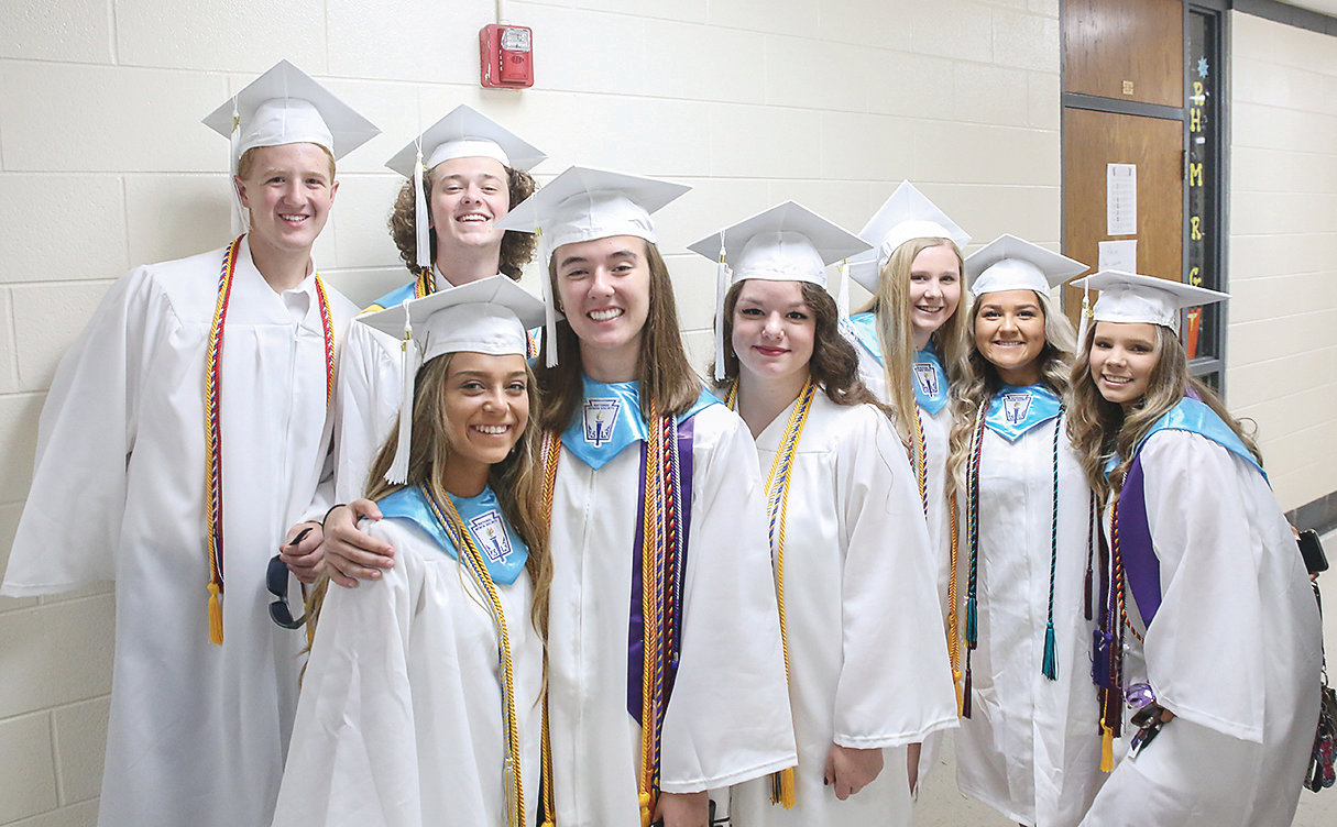 GRADUATION CANDIDATES Hunter Leslie, Luke Lee, Kaylee Logan, Hannah Lombard, Kateryna Makydon, Katie McBride, Jessica McCormick and Maddi McCracken huddle together for a photo prior to graduation.