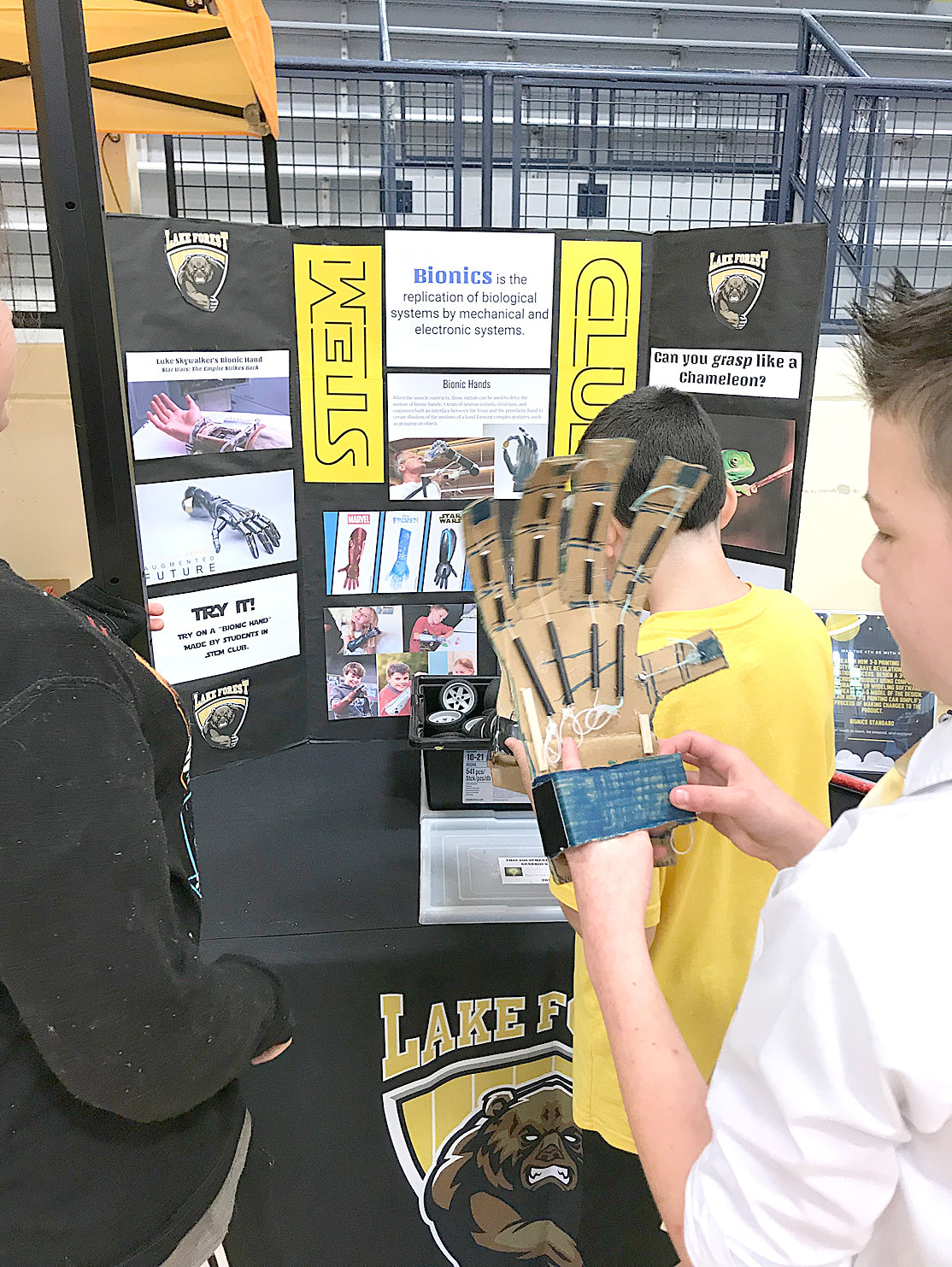 "A STUDENT tries out a ""bionic hand"" made by students at Lake Forest Middle School during STEM on the Greenway."