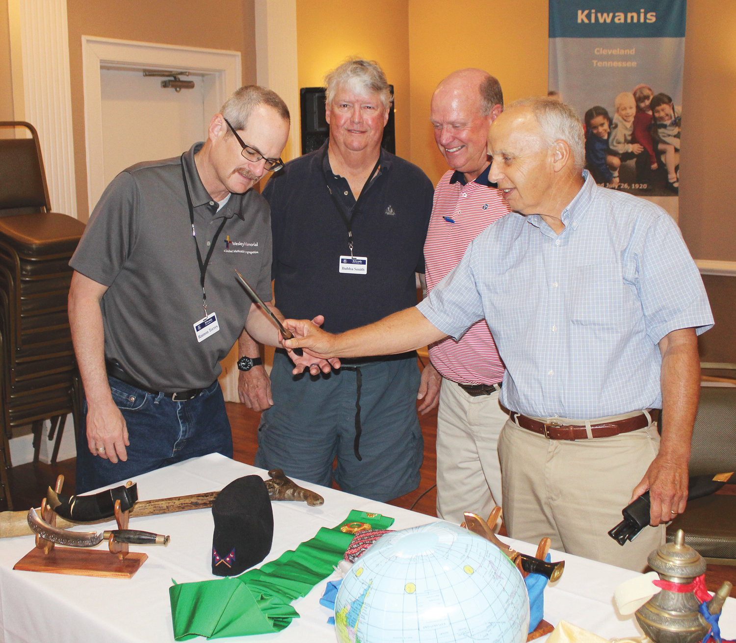 CLEVELAND KIWANIS Club President Ramon Torres, left, checks out a knife brought back from rural Nepal during a Far East mission trip by members of First Baptist Church. Others viewing the keepsake are Program Chairman Bubba Smith, second from left, Jim Gibson, second from right, and Dave Gregory, both with First Baptist.