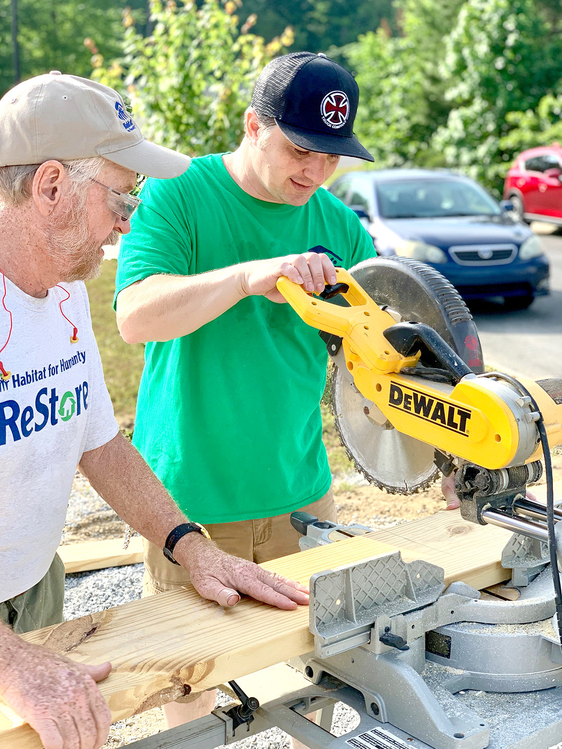 CORE VOLUNTEER DAVE FLOWER observes future Habitat homeowner Victor Headrick, right, sawing wood for his future house at the 2019 Leaders' Build.