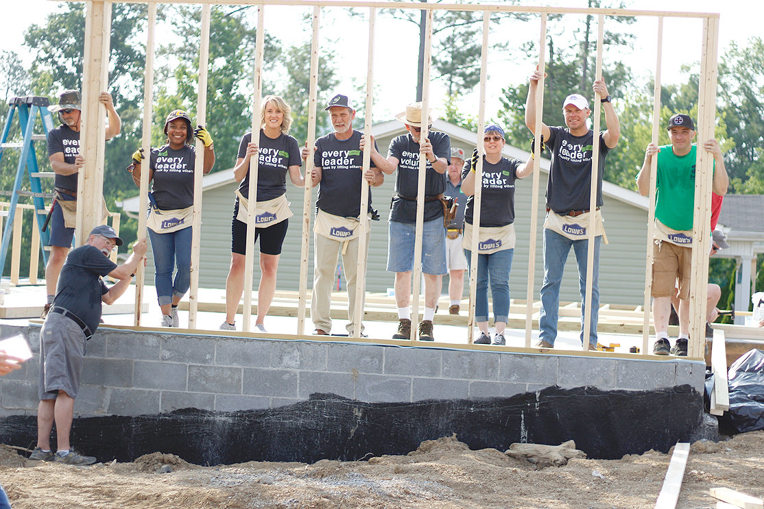 COMMUNITY LEADERS proudly hold up one of two walls they were able to raise on Thursday, May 30, as they work the early shift of the 2019 Habitat Leaders' Build.