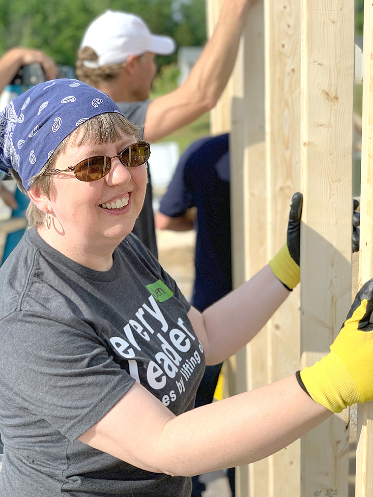 THE REV. JEN NEWELL, pastor of First Cumberland Presbyterian Church, grins as she helps push up the frame of Habitat Home No. 138.