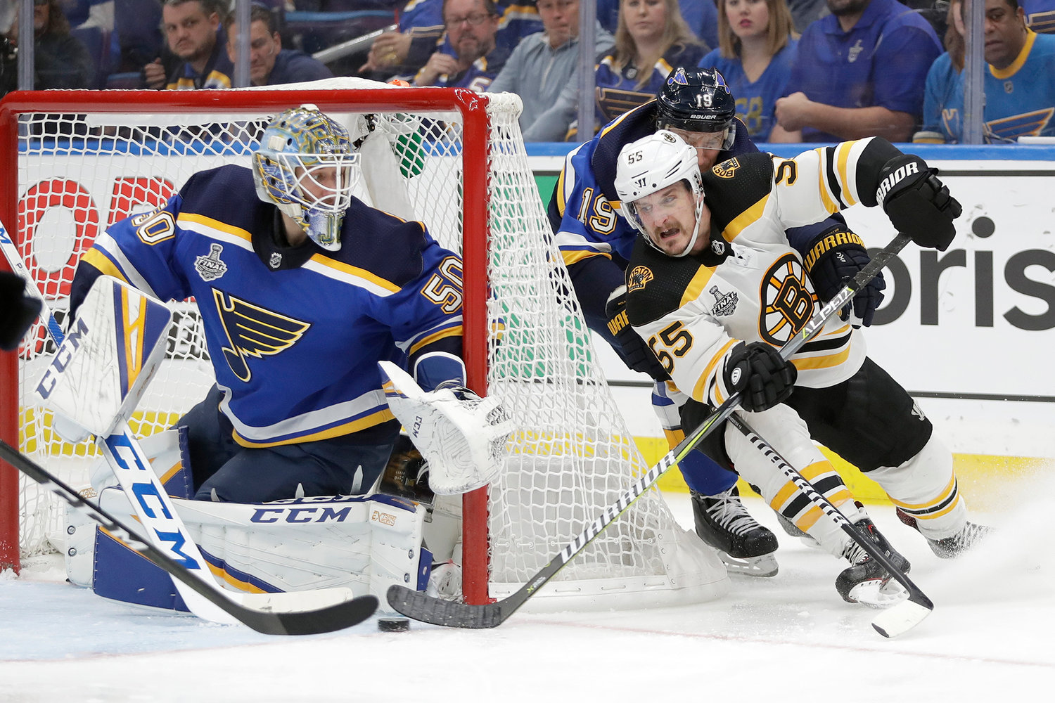 Boston Bruins center Noel Acciari (55) rounds the net against St. Louis Blues goaltender Jordan Binnington (50) during the third period of Game 6 of the NHL hockey Stanley Cup Final Sunday in St. Louis. The Bruins won 5-1 to  the series 3-3.