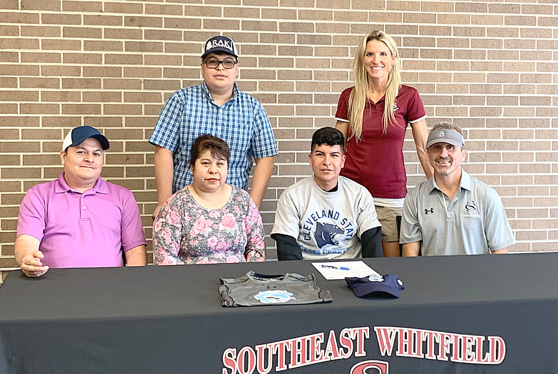 CLEVELAND STATE has signed Southeast Whitfield cross country runner Diego Guzman, seated, second from right, to run cross country for head caoch David Kile, far right, and the Cougars.