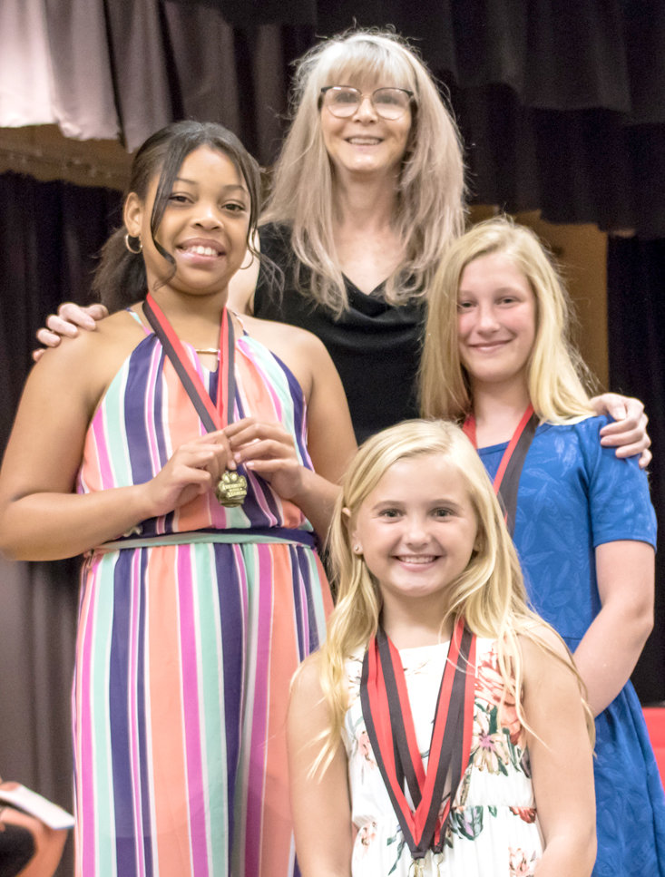 LIBRARY AWARDS were presented to George R. Stuart Elementary fifth-graders Nanielle Walker, Macy Butler and Eva Lipscomb by Edie May.