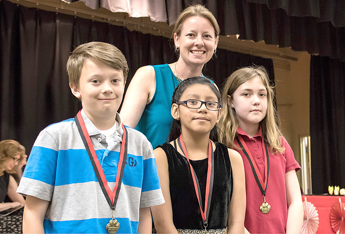 MATH AWARDS were presented to George R. Stuart Elementary fifth-graders Eli Gallaher, Jacky Espinosa and Kendall Cunnyngham. Presenting the awards is Christina Melton.