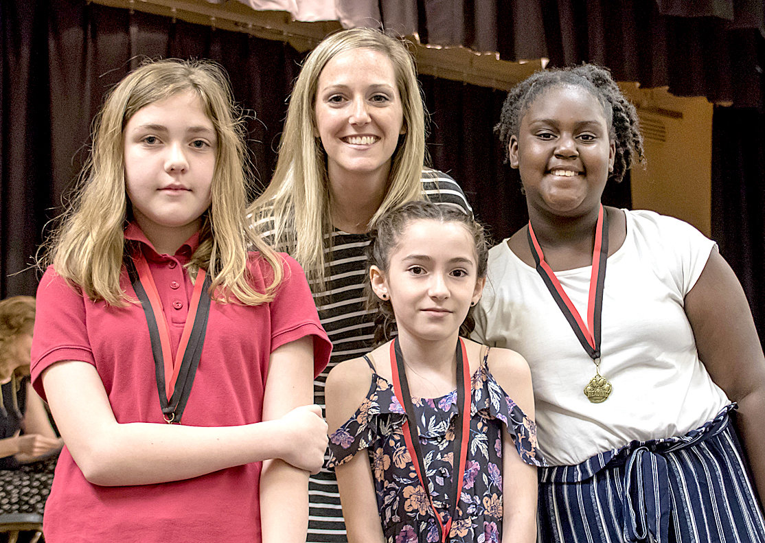 READING AWARD recipients Kendall Cunnyngham, Sophie Nunez-Flores and Jordin Bradford receive their awards from Megan Martin during the Fifth Grade Awards at George R. Stuart Elementary.