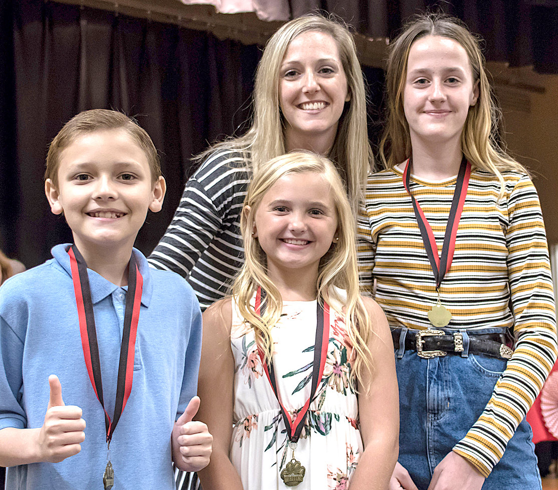 WRITING AWARDS were presented to Steven McKee, Macy Butler and Lily Holder by Megan Martin during the Fifth Grade Awards at George R. Stuart Elementary.