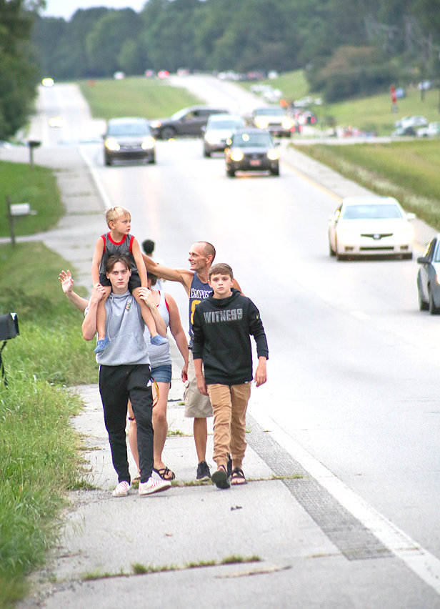 A FAMILY WALKS ALONG the road on their way to FleaLand FleaMarket, the home base for the fireworks show on Thursday evening.