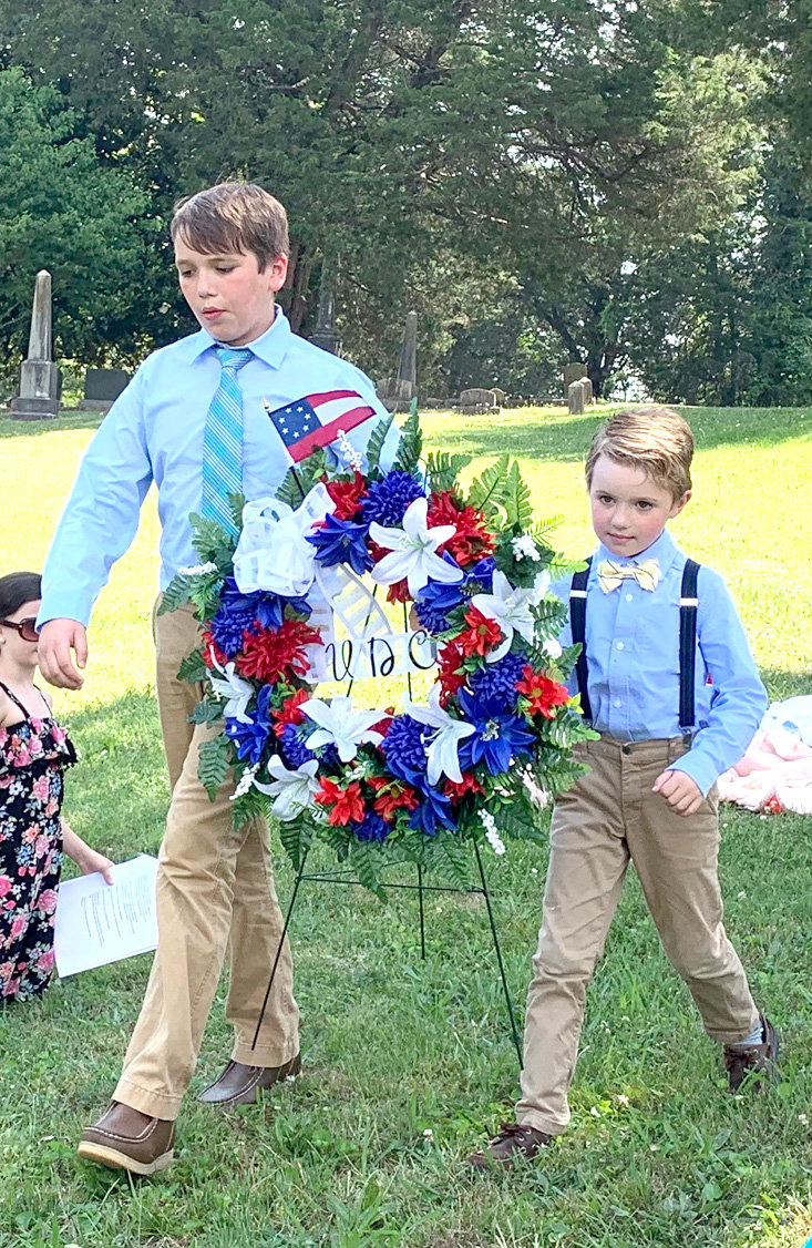 Luke and Ethan Peden lay a wreath during a memorial service at the Fort Hill Cemetery.