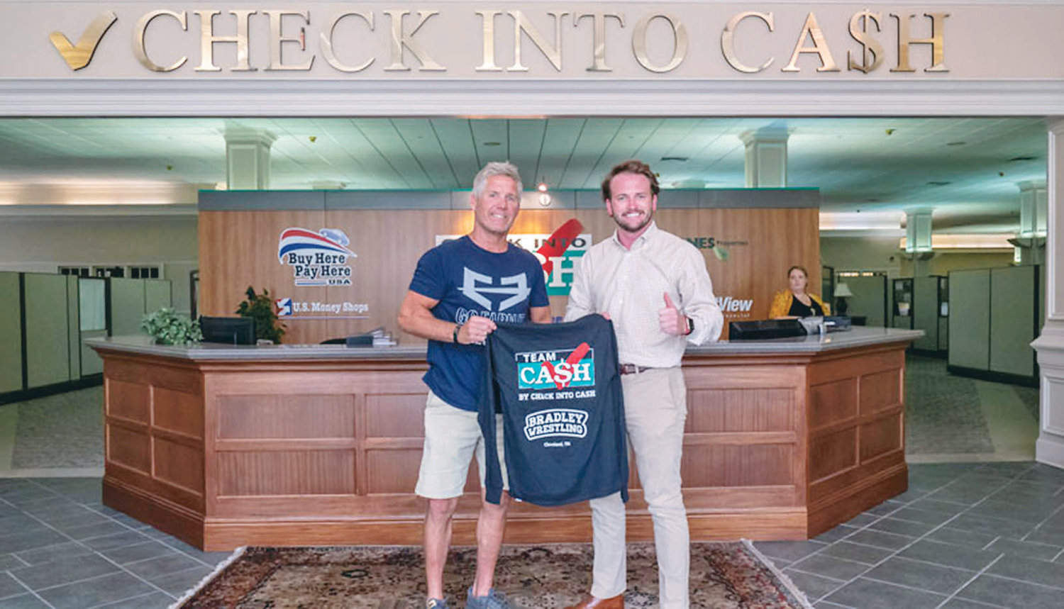 BRADLEY PRIDE Youth Wrestling Coach Steve Logsdon, left, is presented with a Team Cash T-shirt and contribution from Check Into Cash and the Allan Jones Foundation. Pictured with Logsdon is J. Bailey Jones, Vice President at Check Into Cash.