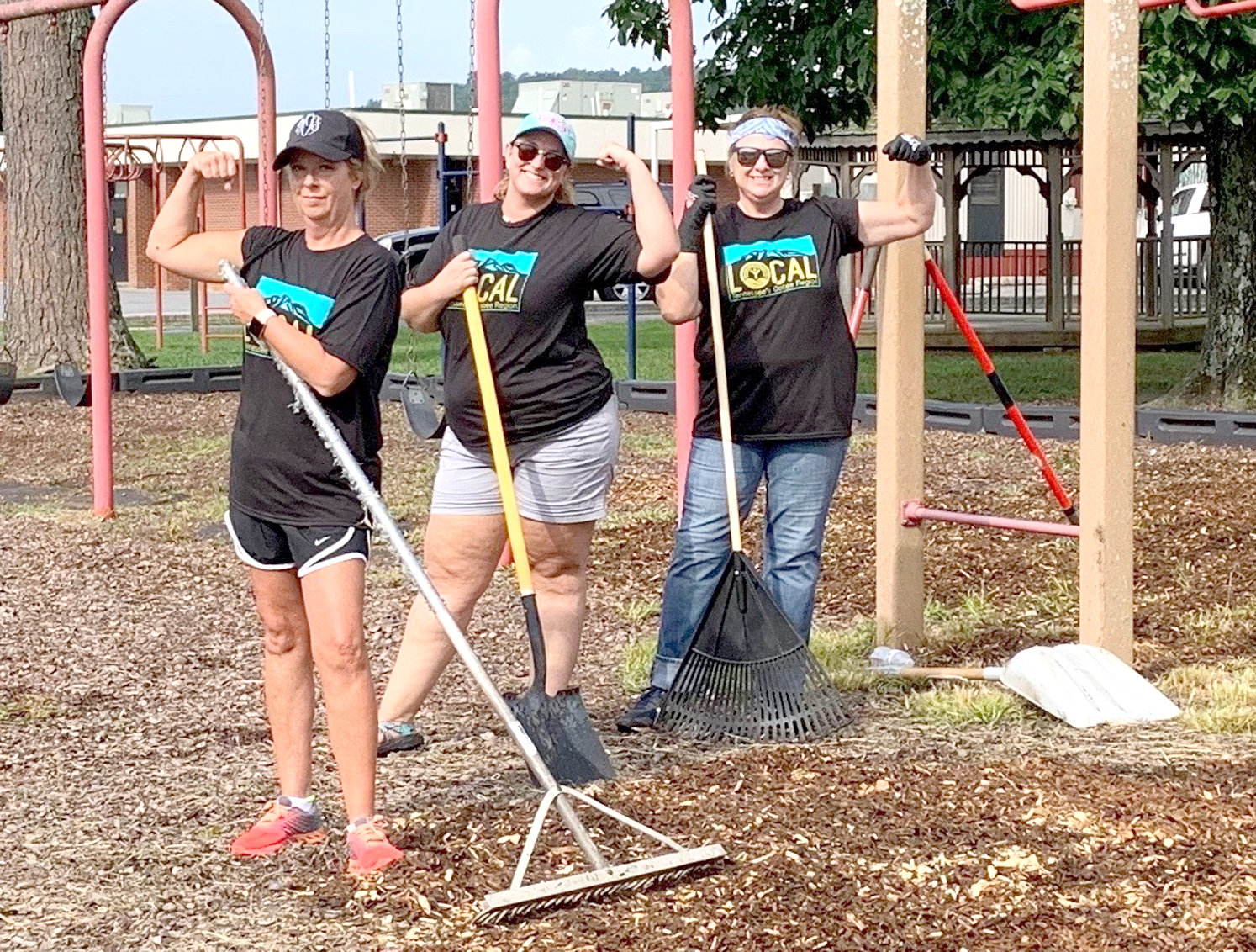 A team of volunteers from Whirlpool in Cleveland take a break from mulching the playground at Taylor Elementary School to show off their muscles. The project was part of a county-wide effort to help nonprofits during the United Way Day of Action.