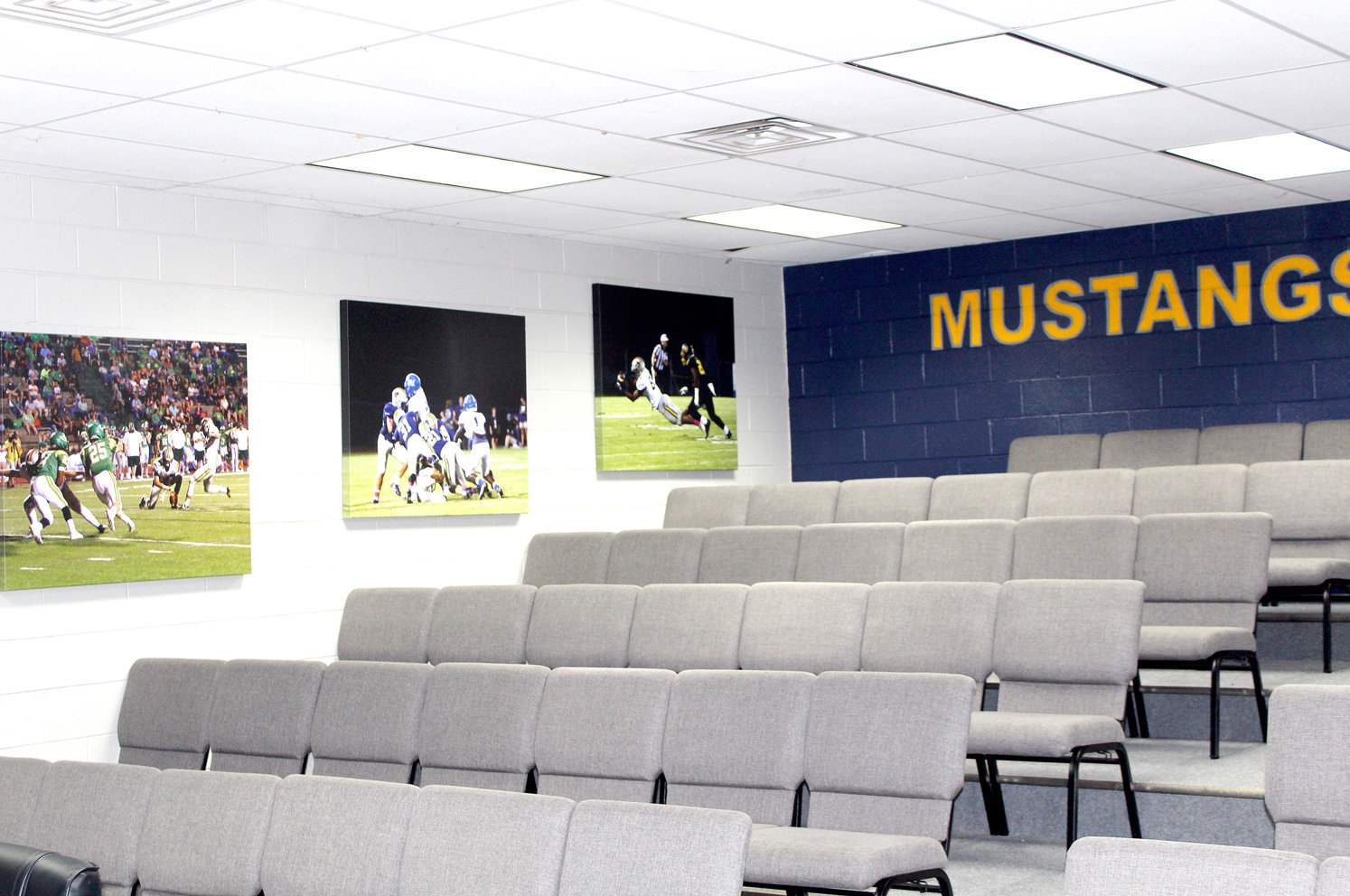 "PHOTOS OF Mustangs in action line both sides of the newly refurbished ""War Room"" inside the Walker Valley football field house."