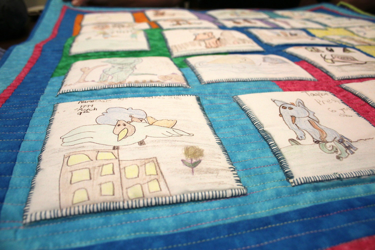 """TAYLOR'S PAPPYLAND ARTWORK"" is a memory quilt sewn by Sandra Presley that consists of doodles and pictures her daughter, Taylor, now 26 years old, drew as she watched the show ""Pappyland"" when she was younger."