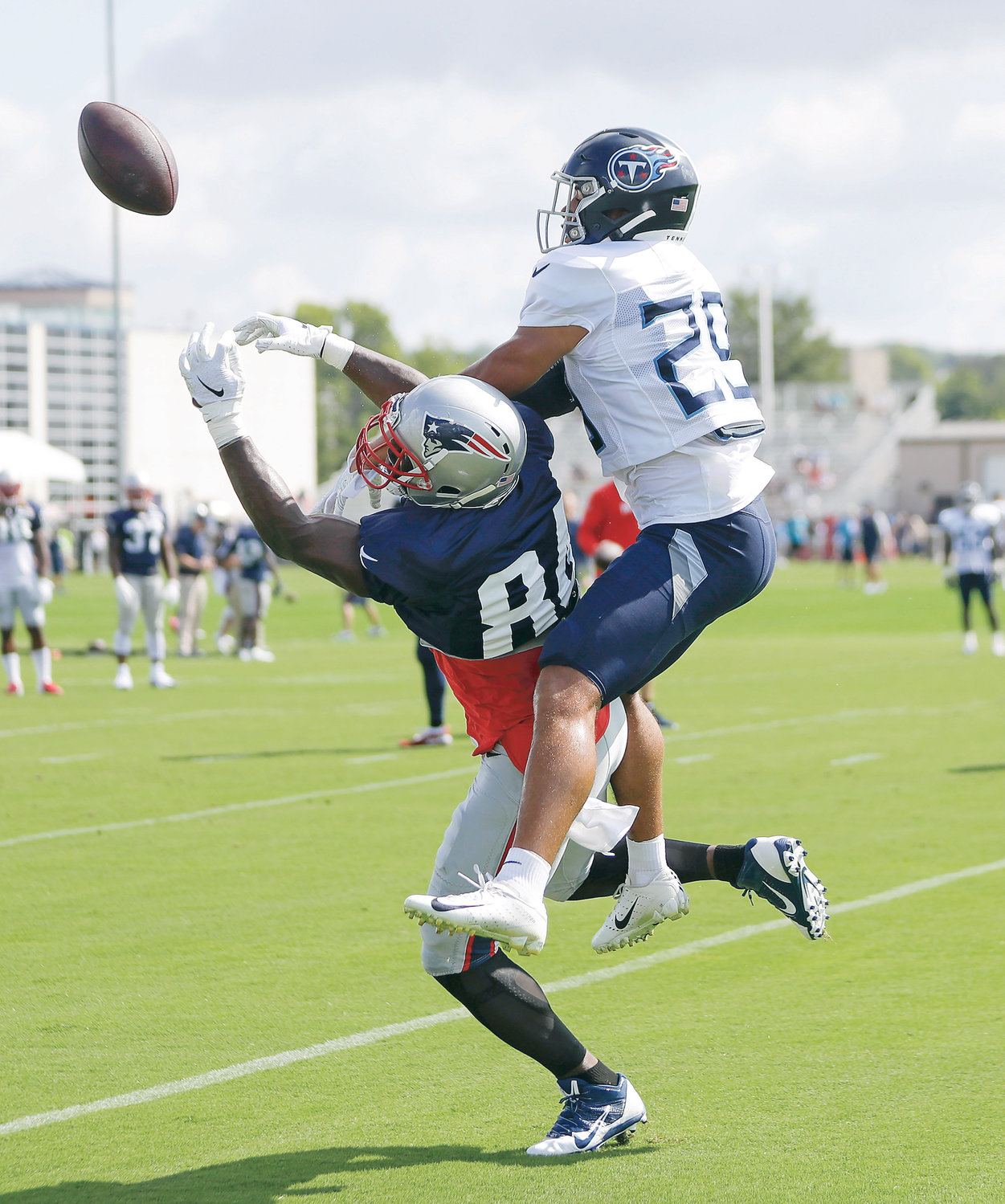 TENNESSEE TITANS defensive back Dane Cruikshank (29) breaks up a pass intended for New England Patriots tight end Ben Watson (84) during a combined training camp Wednesday, in Nashville.