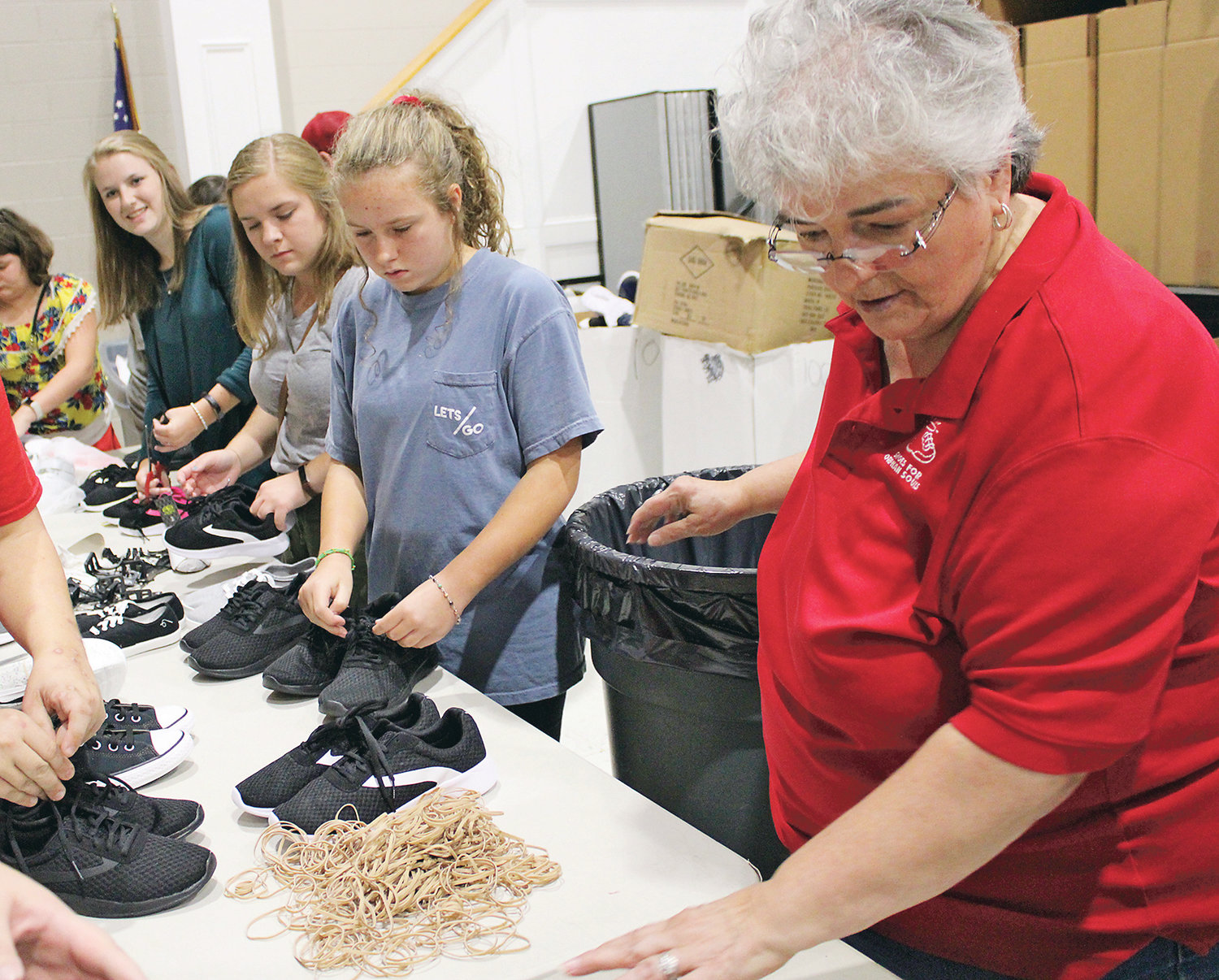 LEAD COORDINATOR BOBBIE REAGAN, right, helps a team of volunteers pair shoes with rubber bands before packing them into boxes for the annual Shoes for Orphan Souls drive. This shoe-packing event took place at the end of last year's campaign.