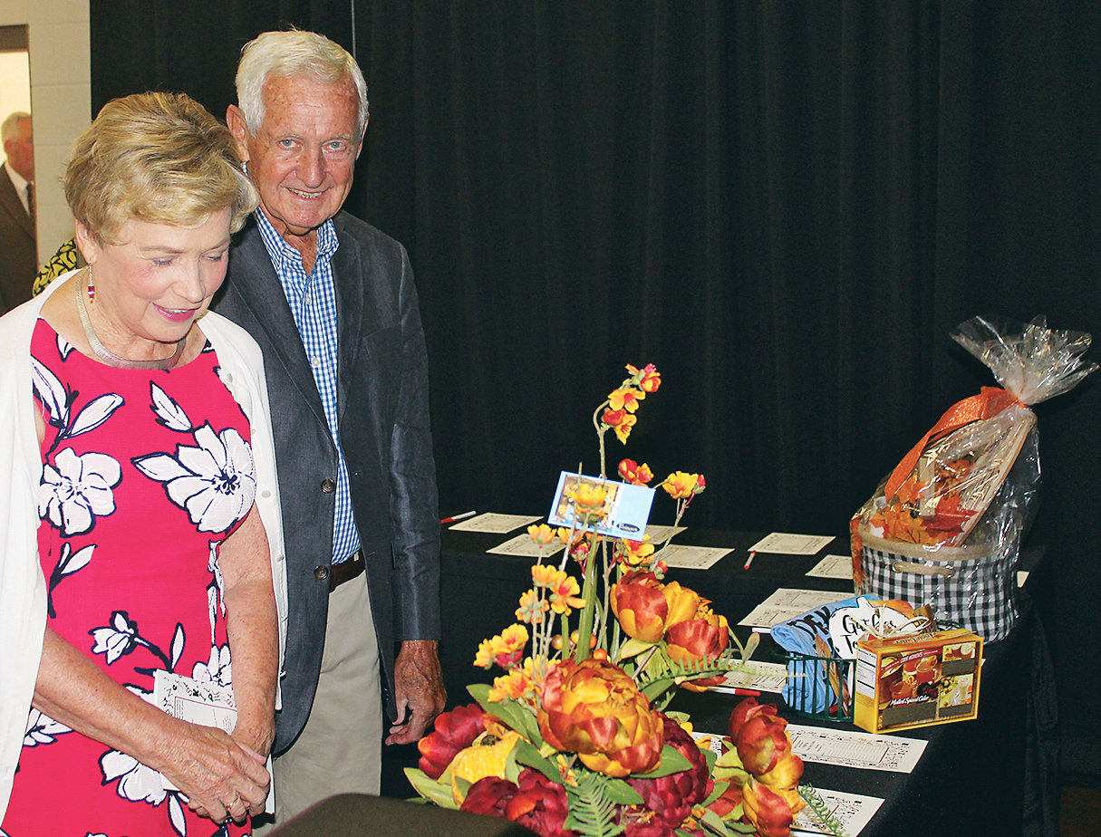 JOE AND PEGGY PESTERFIELD view some colorful silent auction items at Saturday's Trek Thru Truth Gala at the Church of God Ministry Training Center. More than 150 attended the event, hearing a progress update from founder Doug Caywood on the proposed children's Biblical museum.