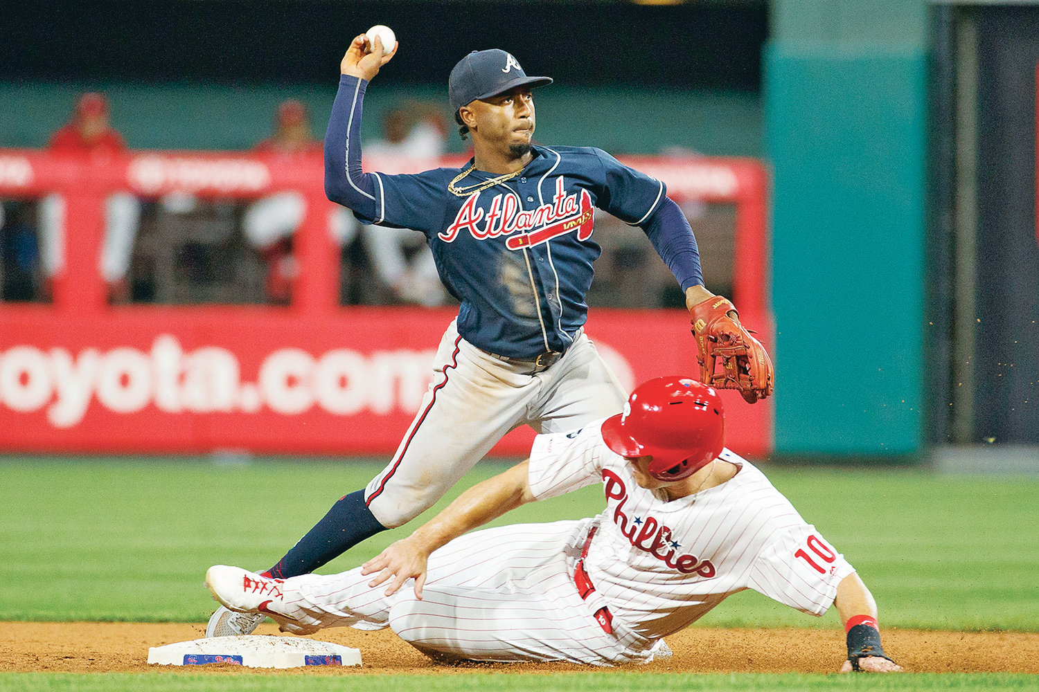 ATLANTA BRAVES second baseman Ozzie Albies throws to first after forcing Philadelphia Phillies' J.T. Realmuto (10) out at second in the ninth inning Monday, in Philadelphia.