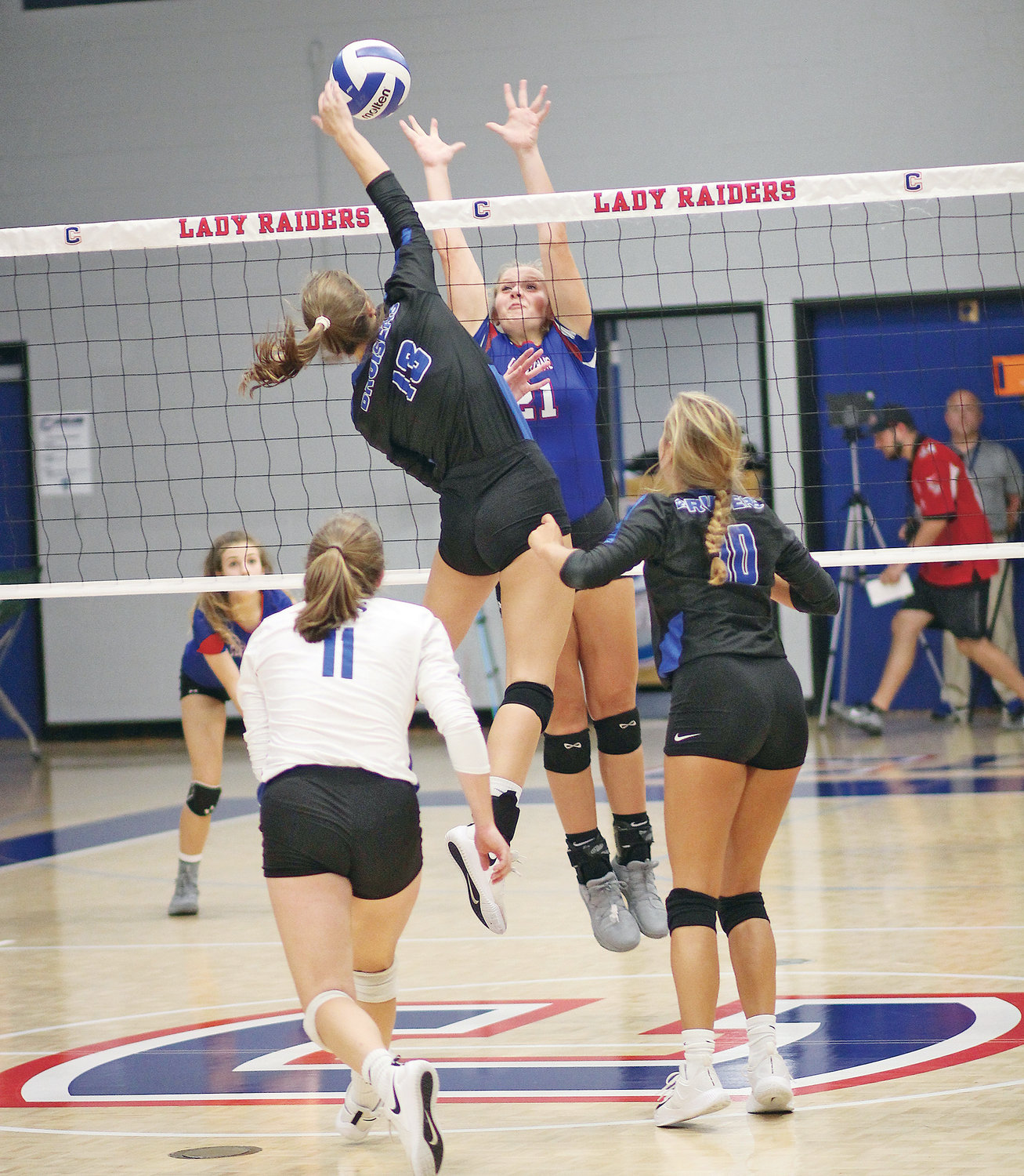 LADY RAIDERS middle blocker Jordan Whitcraft (21) goes for a block against GPS Monday, inside the volleyball gym at Cleveland High School.