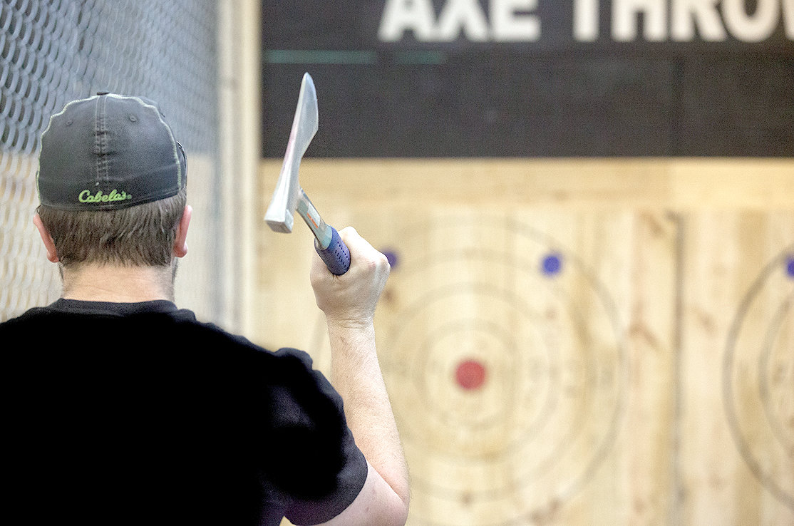 CHAD EINARSEN, co-owner of Axetreme Arena in Cleveland, winds up to throw an ax at a target.