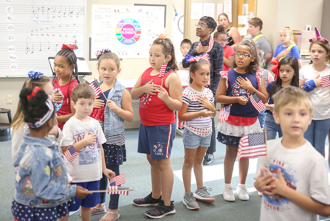 "GLORIA SCOTT RICHMOND, center, Blythe-Bower Elementary music teacher, leads homeroom representatives in the singing of the ""Star-Spangled Banner"" during their celebration on Friday."
